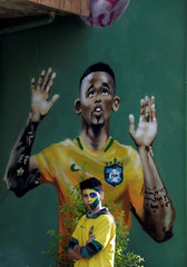 A fan stands next to the painted image of Brazilian soccer player Gabriel Jesus in the neighbourhood where Gabriel Jesus lived in his childhood in Sao Paulo