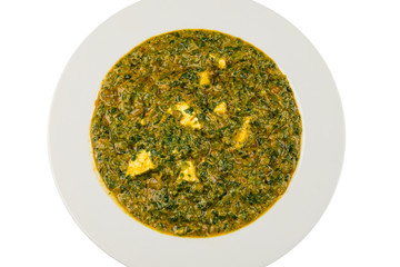 Indian vegetarian dish cheese spinach or palak saag paneer curry on white plate isolated from background