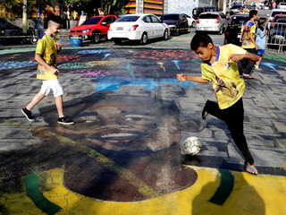 Children play soccer on a street painted with the image of Brazilian soccer player Gabriel Jesus in the neighbourhood where Gabriel Jesus lived in his childhood in Sao Paulo