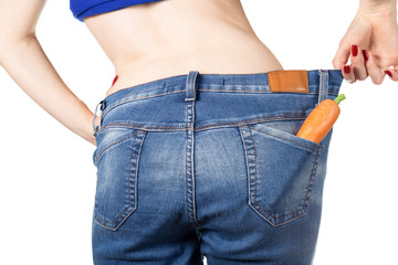 Weight loss and healthy eating or dieting concept. Slim girl in oversized jeans with a carrot in the pocket. Rear view. Close shot.