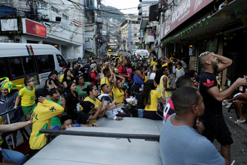 Fans react as they watch the broadcast of the FIFA World Cup Group E soccer match between Brazil and Switzerland, at Rocinha slum in Rio de Janeiro
