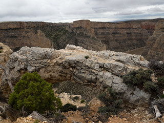 A View of the Bighorn Canyon through an opening in a natural stone arch.