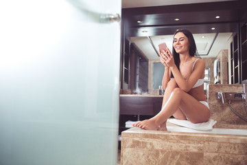 Full length portrait of delighted young woman enjoying time in bathroom. She is sitting on bath towel and chatting on phone with smile and enthusiasm. Copy space in left side