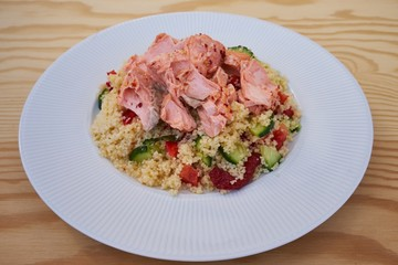 Detailed Picture of the fresh, tasty and healty couscous salad with poached salmon served on the simple white plate like light diner or lunch ideal for reduction diet.