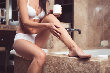Close up of female hand moisturizing body in bathroom. She is sitting on bath and holding cosmetic jar while gently touching leg with hand