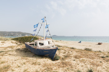 Old wooden fishing boat on the beach with Greek flags on the mast. Naxos island, Greece