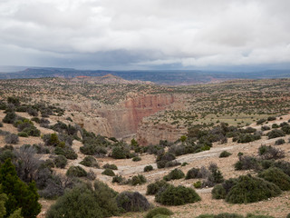 The Bighorn Canyon with rocky terrain in the foreground, clouds overhead and mountains in the distance.