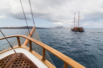 Old wooden ships sailing in Mediterranean sea towards the volcano caldera. View from the bow of the ship.
