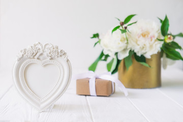 Heart shaped photoframe with plaster flowers,gift box with ribbon and vintage bowl with white peonies bouquet on the wooden table. Love background. Greeting card. Copy space, selective focus.