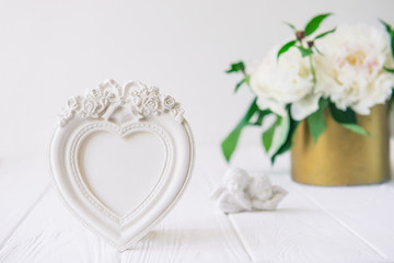 Heart shaped photoframe with plaster flowers, statuette of two antique little lovely angels on the white wooden table with bouquet of white peonies. Love background. Copy space, selective focus.