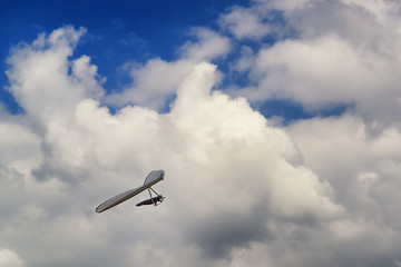 Hang glider pilot soar in thermal updrafts below the clouds.