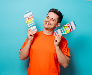 Young handsome man in orange t-shirt with sandals. Studio image on blue background