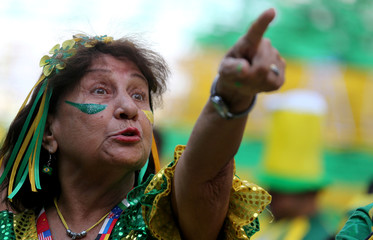 A fan reacts as she watches the broadcast of the World Cup Group E soccer match between Brazil and Switzerland, in Rio de Janeiro
