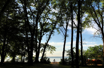 Woman enjoys a summer day as she rides a bicycle near a lake on the outskirts of Minsk