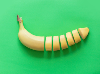 Yellow cut banana isolated on green background. Natural light