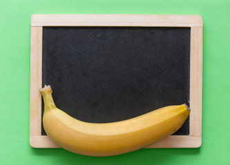 Yellow banana with blackboard on green background. Natural light