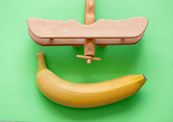 Yellow banana with toy wooden airplane on green background. Natural light