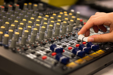 Hand of woman adjusts equalizer on mixing console. Sound engineer working on professional audio mixer. Music recording studio concept