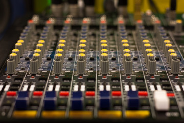 Close up on professional audio mixer. Mixing desk, sound board. Blue, yellow and red controls and equalizers. Film and music studio recording equipment