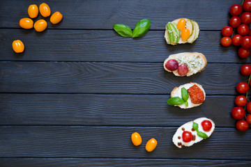 appetizer bruschettas with tomatoes, salmon, creamy cheese, basil, grapes, blue cheese, pear, avocado with fresh cherries tomatoes on black wooden background. Italian cuisine, top view, copy space.
