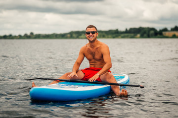 a man in shorts sitting relaxed on   sup surf
