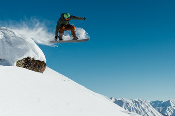 snowboarder in the outfit drops off the ledge of the stone onto the fresh snow creating a spray of snow Wall mural