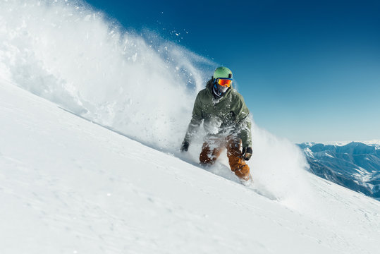 male snowboarder curved and brakes spraying loose deep snow on  freeride slope