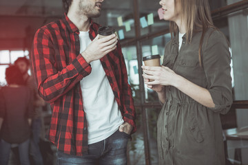 Coffee break. Young involved man and woman are standing in office and talking while male is holding hand in pocket of his jeans. They are drinking fresh espresso. Focus on their arms with paper cups