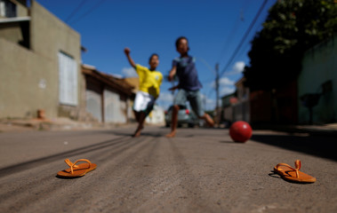 Children play soccer before the World Cup Group E soccer match between Brazil and Switzerland, at Sao Sebastiao neighbourhood in Brasilia
