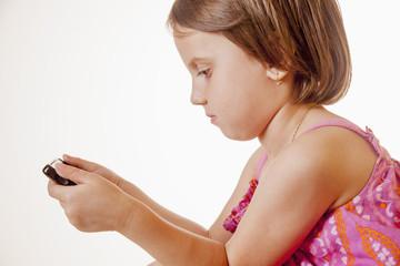 Social Media addiction. Little child girl holding smart phone (psychological problems, media mania, education concept)