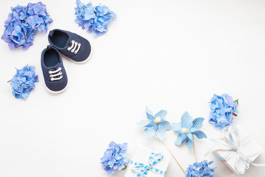 Cute newborn baby boy shoes with festive decoration. Baby shower, birthday, invitation or greeting card mockup