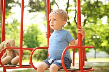 Cute little boy playing on swings in park
