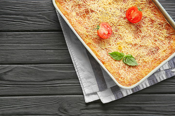 Baking tray with tasty spinach lasagna on wooden table