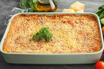 Baking tray with tasty spinach lasagna on table