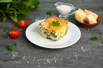 Plate with piece of tasty spinach lasagna on table