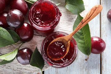 Glass jars with delicious plum jam on wooden background