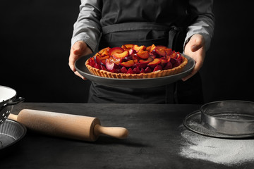 Woman holding delicious pie with plums on black background