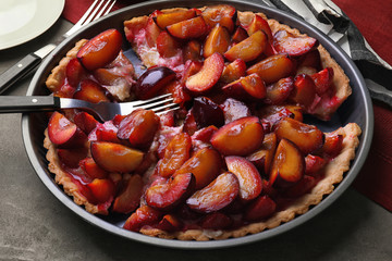 Delicious pie with plums on table