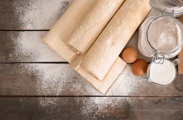 Raw flaky dough with flour on table