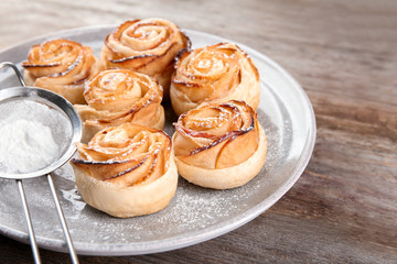 Plate with apple roses from puff pastry on wooden background