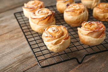 Cooling rack with apple roses from puff pastry on wooden background