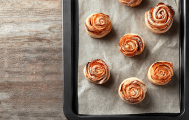 Baking tray with apple roses from puff pastry on wooden background
