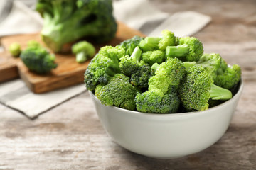 Bowl with fresh green broccoli on table