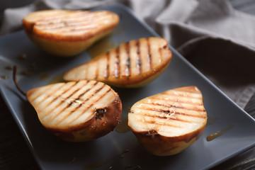Tasty baked pears on plate