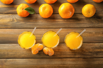 Composition with fresh mandarins and citrus juice on wooden table