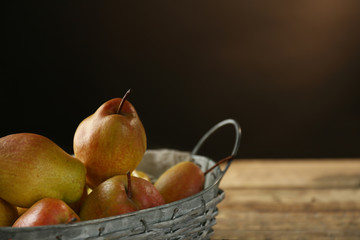 Basket with delicious pears on blurred background