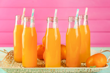 Bottles with fresh citrus juice on tray