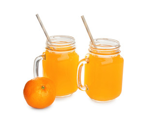 Mason jars with fresh citrus juice and tangerine on white background