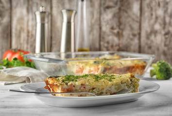 Plate with tasty broccoli casserole on table. Fresh from oven