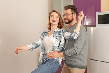 Lovely couple dancing together in kitchen